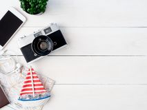 Travel concept with retro camera films, map, passport, smartphone on white wooden with copy space, Tourist essentials,. Top view travel concept with retro camera stock image
