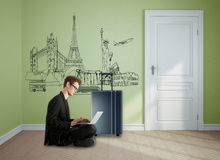Travel concept. Side view of young businessman sitting on floor and using laptop in green room interior with suitcase. Travel concept. 3D Rendering Stock Photography