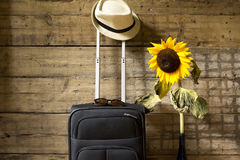 Travel concept. Suitcase, hipster hat, sunflower and sunglasses on wooden wall background. Stock Photo
