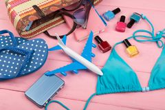 Travel concept - summer women`s fashion with bag, blue swimsuit, sunglasses, flip flops, nail polish, note pad and little airplan. E and suitcase on pink wooden stock photos