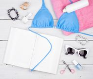blue swimsuit, book, pink towel, cosmetics makeup, bijou and essentials on white wooden desk royalty free stock photos