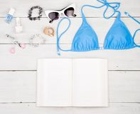 blue swimsuit, book, sunglasses, cosmetics makeup, bijou and essentials on white wooden desk stock photography