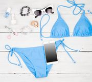 blue swimsuit, smart phone, cosmetics makeup, bijou and essentials on white wooden desk royalty free stock photography
