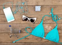 Blue swimsuit, smart phone, sunglasses, headphones, gift box and shopping carts on brown wooden table. Travel concept - summer women& x27;s fashion with blue Stock Photo