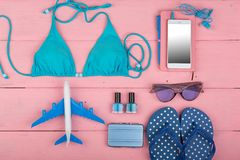 Travel concept - summer women's fashion with blue swimsuit, sunglasses, smart phone, flip flops little airplane and suitcase royalty free stock image