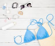 blue swimsuit, yellow shorts, cosmetics makeup, bijou and essentials on white wooden desk stock photos