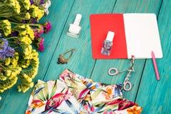 Summer women set with dress, colorful flowers, cosmetics makeup,. Travel concept - summer women set with dress, colorful flowers, cosmetics makeup, notepad Stock Image