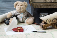 Travel concept, teddy bear with old binoculars and suitcase on the antique map with letter and a fountain pen Stock Photos
