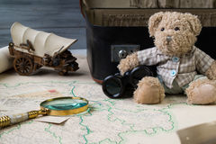 Travel concept, teddy bear with old binoculars and suitcase on the antique map with magnify glass. Travel concept, cute teddy bear with old binoculars and Royalty Free Stock Image