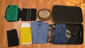 Travel concept timelapse of clothes packing into travel suitcase stock footage