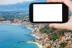 Tourist photographs shore with Giardini Naxos. Travel concept - tourist photographs Ionian sea shore with Giardini Naxos town in Sicily Italy in summer season on Stock Image