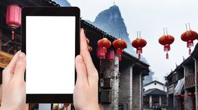 Tourist photograps Xing Ping town in China. Travel concept - tourist photograps street in Xing Ping town in Yangshuo county in China in spring on tablet with cut Royalty Free Stock Photos