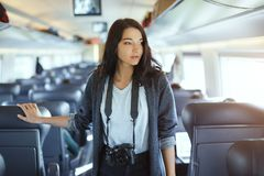 Travel concept. Tourist woman with dslr camera in train. stock photo