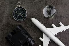 Travel concept with toy airplane, binoculars, compass and globe. On black background Stock Images