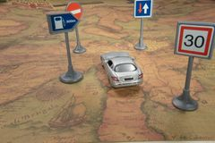 Travel concept. Toy car on vintage World map with road sign royalty free stock photo