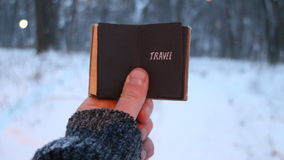 Travel concept, traveler holds a book in his hand with the inscription. On the background of the winter forest stock video