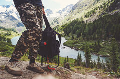 Travel concept: Trekker with tourist sticks and backpack on lake royalty free stock photos