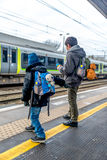 Travel concept of two boys on train station platform Stock Image