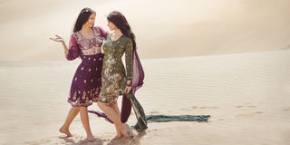 Travel concept. Two gordeous women sisters traveling in desert. royalty free stock photo