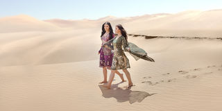Travel concept. Two gordeous women sisters traveling in desert. Arabian Indian movie stars. royalty free stock image