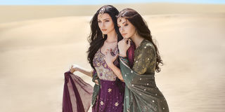 Travel concept. Two gordeous women sisters traveling in desert. Arabian Indian movie stars. royalty free stock photos