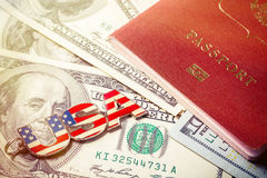 Travel concept. USA key fob on hundred dollar banknotes with passport document Stock Photos