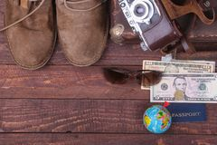 Travel concept with Vintage suitcase, sunglasses, old camera, suede boots, case for money and passport on wooden floor. Stock Photo