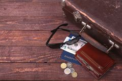 Travel concept with Vintage suitcase, sunglasses, old camera, suede boots, case for money and passport on wooden floor. Stock Image