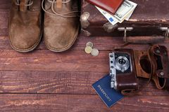Travel concept with Vintage suitcase, sunglasses, old camera, suede boots, case for money and passport on wooden floor. Travel concept with Vintage suitcase Royalty Free Stock Photo