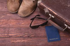 Travel concept with Vintage suitcase, sunglasses, old camera, suede boots, case for money and passport on wooden floor. Royalty Free Stock Photography