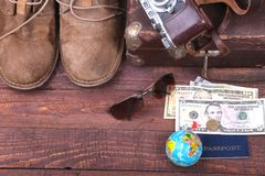 Travel concept with Vintage suitcase, sunglasses, old camera, suede boots, case for money and passport on wooden floor. Royalty Free Stock Photo
