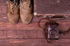 Travel concept with Vintage suitcase, sunglasses, old camera, suede boots, case for money and passport on wooden floor. Travel concept with Vintage suitcase stock photos