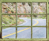 Travel concept - windy road through old window Stock Images