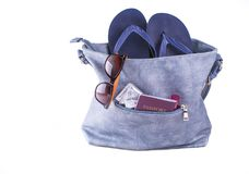 Travel concept. Woman bag with beach slippers, sunglasses, passport, condoms, lipstick.  Royalty Free Stock Images