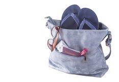 Travel concept. Woman bag with beach slippers, sunglasses, passport, condoms, lipstick.  Stock Photo