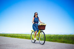 Travel concept - woman riding vintage bicycle in countryside Stock Photography