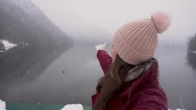 Travel concept. Woman taking selfie and showing Ritsa lake in Abkhazia in winter stock video footage