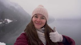 Travel concept. Woman showing thumb up at Ritsa lake in Abkhazia in winter. stock video