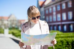 Travel concept - woman tourist looking at the map stock image