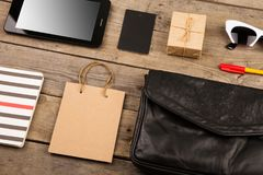 Women set with bag, tablet pc, sunglasses, notepad, gift box, shopping bag and tag on brown wooden desk. Travel concept - women set with bag, tablet pc Royalty Free Stock Photos