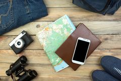 Travel concept on wooden table. Top view image of travel accessories with washed out vintage filter effect. stock photography
