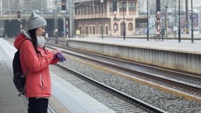 Travel concept - Young beautiful girl waiting for a late train on the railway station and looking at the clock. It is stock video