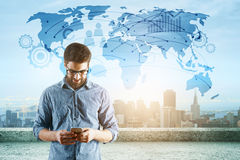 Travel concept. Young businessman using cellphone while standing on concrete rooftop with city view and map. Travel concept Stock Photos