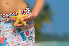 Travel concept. Young girl holding a starfish in his hand on a b Royalty Free Stock Photo