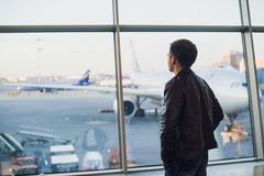 Travel concept with young man in airport interior with city view and a plane flying by. Stock Photo