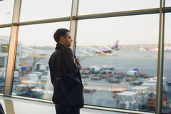 Travel concept with young man in airport interior with city view and a plane flying by. stock photos