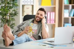 Travel concept. Young man talking by mobile phone sitting. At workplace Royalty Free Stock Photo