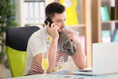 Travel concept. Young man talking by mobile phone  sitting at workplace. Travel concept. Young man talking by mobile phone sitting at workplace Royalty Free Stock Images
