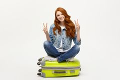 Travel concept: young smiling caucasian woman siting on suitcase showing two fingers. over white background. Travel concept: young smiling caucasian woman stock photography