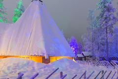 Travel Concepts and Ideas. Marvelous Lapland Houses in Suomi Vil. Lage in Front of Marvelous Highlighted Winter Forest Scenery.Horizontal Shot Royalty Free Stock Photo